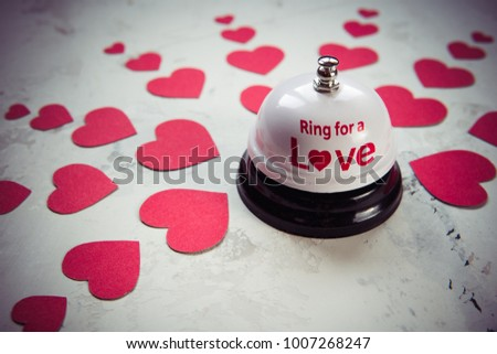Ring bell for a love and many hearts on a wood background. #1007268247