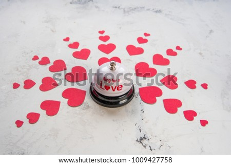 Ring bell for a love and many hearts on a wood background. #1009427758