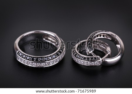 Ring from white gold and an earring with jewels on a black background