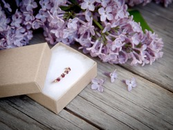 Ring in gift box and lilac on wood