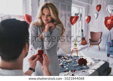 Ring is perfect! Attractive young woman looking at engagement ring with smile while her boyfriend proposing her in the bedroom