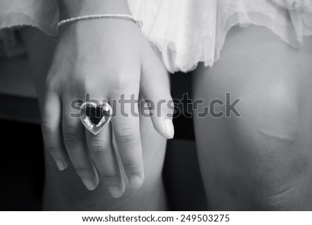 Ring love heart shape inside a young finger  hand in black and white color