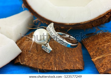 Ring with pearl and diamonds on coconut, jewelry concept