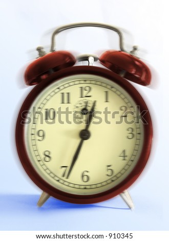 Ringing retro-styled alarm clock - close up on blue background.
