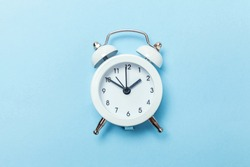 Ringing twin bell vintage classic alarm clock Isolated on blue pastel colorful trendy background. Rest hours time of life good morning night wake up awake concept. Flat lay top view copy space