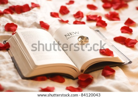 Rings On The Bible; Wedding Rings On The New Testament Bible Surrounded By Rose Petals