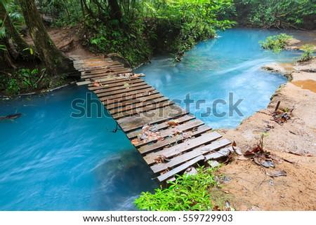 Rio celeste and small wooden bridge Tenorio national park Costa Rica Foto d'archivio ©