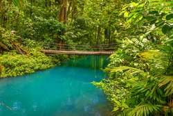 Rio Celeste with turquoise, blue water and small wooden bridge Tenorio national park Costa Rica. Central America.
