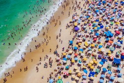 Rio de Janeiro, Brazil, aerial view of Copacabana Beach showing colourful umbrellas and people bathing in the ocean on a summer day. Tropical travel and vacation concept.