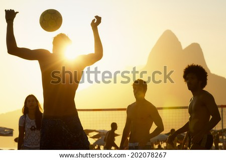 RIO DE JANEIRO, BRAZIL - FEBRUARY 08, 2014: Group of young Brazilians play keepy uppy beach football, known locally as altinho, against a sunset silhouette of Two Brothers Mountain at Posto Nove.