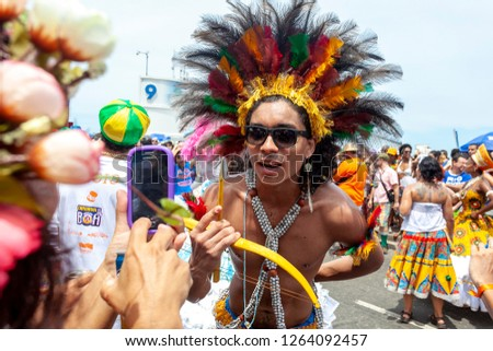 Rio de Janeiro, Brazil - March 4, 2014: Young man with an indian costume looking at a phone camera of a spectator at a carnival block party in the streets of Rio de Janeiro #1264092457