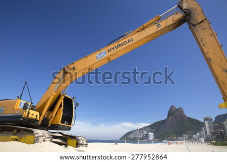 RIO DE JANEIRO/BRAZIL - MAY 11 2015: Excavator works on Ipanema Beach in Rio de Janeriro on May 11, 2015. Ipanema is one of the most famous touristic beaches in Brazil.