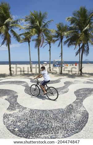 RIO DE JANEIRO, BRAZIL - OCTOBER 19, 2013: Young Brazilian rides his bicycle along the boardwalk at Copacabana Beach.