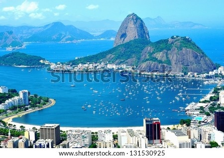 Rio de Janeiro, Olympic City 2016 - Sugar-loaf. Mountain resembling inverted funnel behind Urca hill. Tourist site in the former capital of Brazil.  Water around, and Niteroi city in the background.