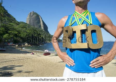 RIO first place athlete wearing gold medals standing outdoors in front of Sugarloaf Mountain Rio de Janeiro Brazil