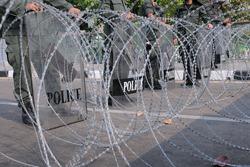 Riot Police Behind Razor Wire