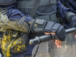 Riot police practice crowd-control scenarios from protesters throwing officers with paint.