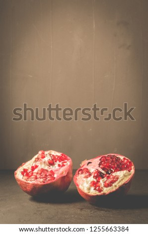 Ripe and juicy pomegranate on rustic dark background/Ripe and juicy pomegranate on rustic dark background with copyspace #1255663384