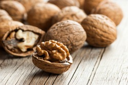 Ripe and raw whole big walnut kernel with thin shell on wooden rustic backdrop. healthy nut food for brain. Fresh walnuts background concept