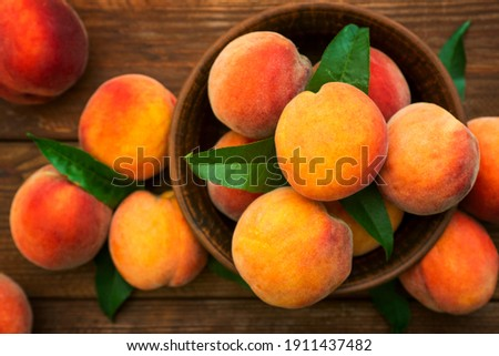 Ripe and tasty and juicy peaches lie on a plate on a wooden table. Large peaches on rustic wooden background, selective focus.