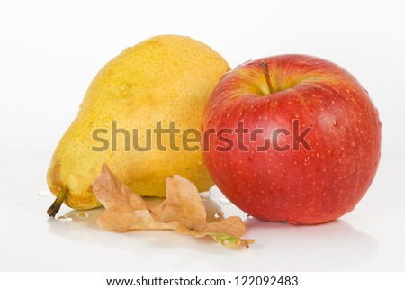 ripe apple and pear with oak leaves and cinnamon on a white background