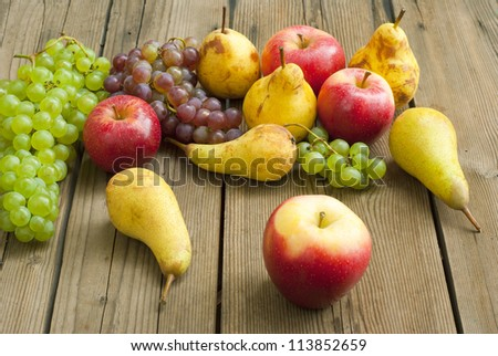 ripe apples, pears and grapes on rustic wooden table