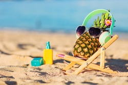 Ripe attractive girl-pineapple in stylish headphones lying on sunbed on the sand against turquoise sea. Listening music, relaxing. Wearing sunglasses. Tropical summer vacation concept. Sunbathing