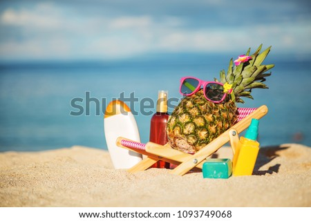 Ripe attractive girl-pineapple lying on sun chair on the sand against turquoise sea. Relaxing. Wearing funny sunglass. Tropical summer vacation concept. Sunbathing using sunscreen lotion. Sun protect #1093749068