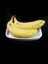 Ripe Banana.  Banana is a healthy source of fiber, vitamin B6, vitamin C and various antioxidant s and phytonutrients.  Black background, isolated, selective focus.