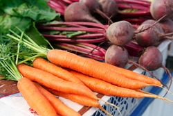 Ripe beet and carrot on the counter of the Belarussian market. Fresh vegetables in the street bazaar.
