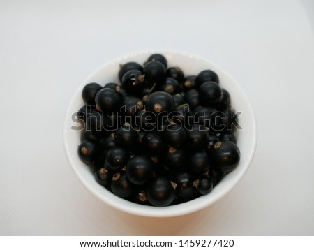 Ripe black currant berries in a small white Cup on a white background. Black currant harvest. Natural vitamin. Healthy food. vegetarian food.