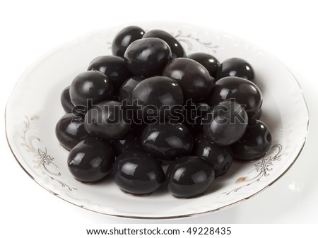 Ripe black olives on porcelain plate