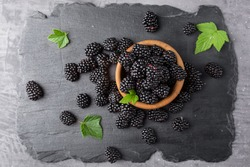 Ripe blackberries with leaves in a bowl on a stone plate. Top view