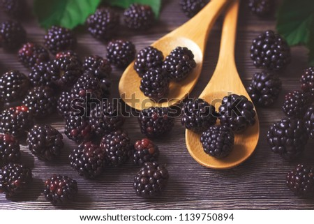 ripe blackberry closeup. blackberry in wooden spoons. blackberry crop.