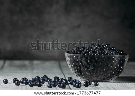 ripe blueberries in a glass transparent plate on a dark background