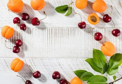 Ripe cherries and fresh apricots on a white wooden background. Summer background. Copy space.