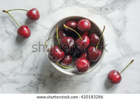 Ripe cherries in bowl on marble table. Top view