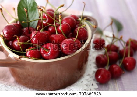Ripe cherries in brown ceramic bowl on light background #707689828