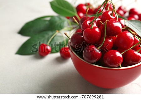 Ripe cherries in red ceramic bowl on light background #707699281