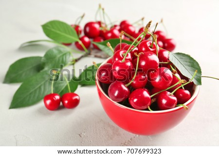 Ripe cherries in red ceramic bowl on light background #707699323