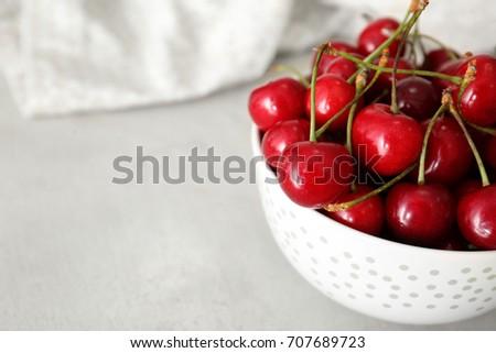Ripe cherries in white ceramic bowl on light background #707689723