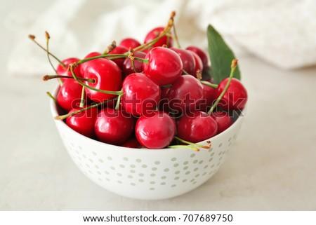 Ripe cherries in white ceramic bowl on light background #707689750