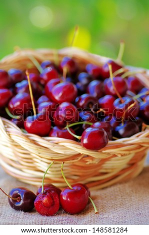 Ripe cherries in wooden basket on green background