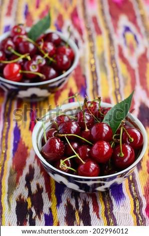Ripe cherry in authentic uzbek tea bowls on bright ethnic fabric