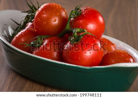 Ripe cherry tomatoes in a bowl on a wooden table