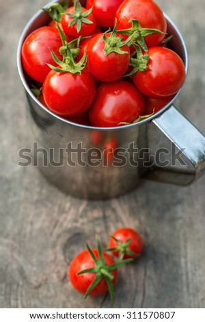 ripe cherry tomatoes on a wooden table in an iron circle