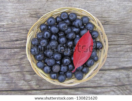 Ripe chokeberry in the basket on wooden background, close-up