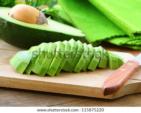 ripe cleaned peeled avocado sliced on the board