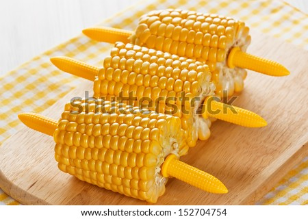 Ripe cobs of sweet corn on wooden background