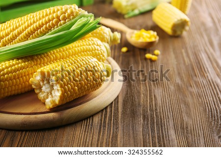 Ripe corn on cutting board on wooden background